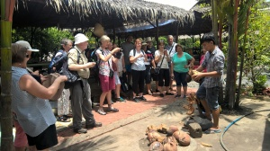Foreign tourists are watching candy coconut making in Mekong Delta